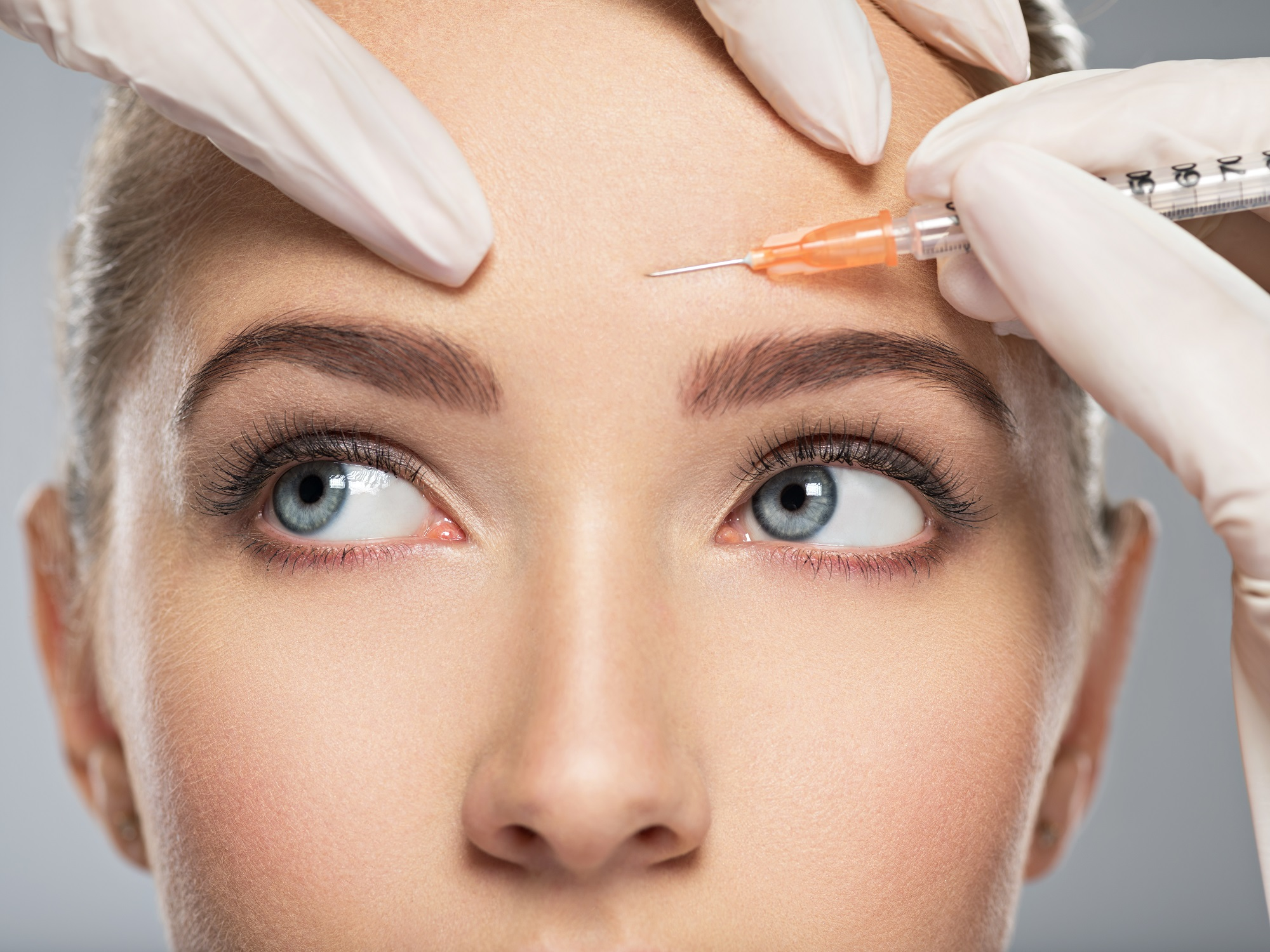 A woman receiving a botox injection in her forehead