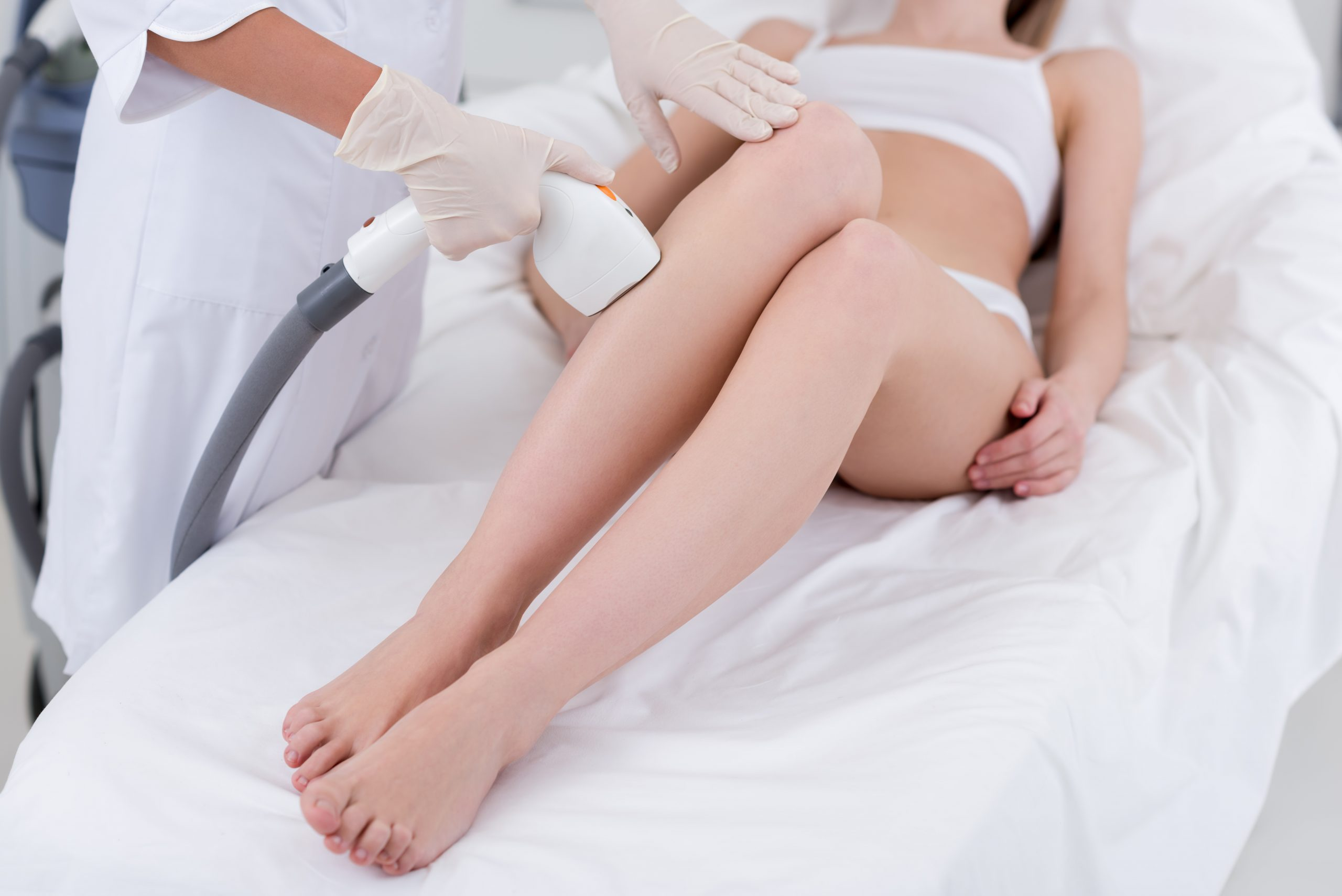 a woman receiving laser hair removal treatment on her legs